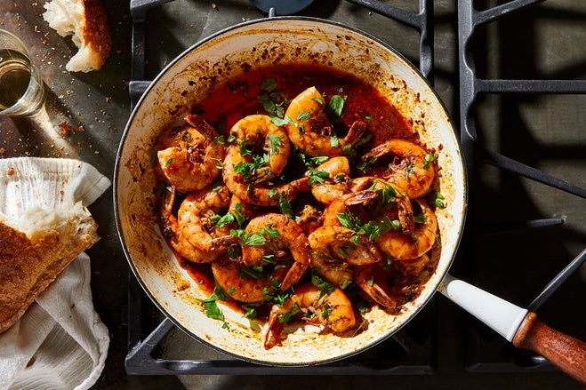 A pot filled with cooked shrimp coated in red sauce and topped with chopped parsley.