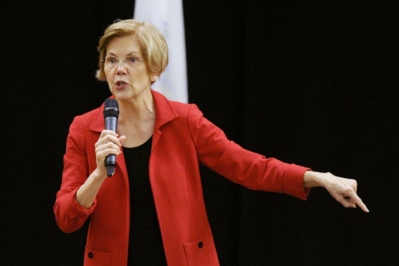 Sen. Warren, dressed in a red jacket, holds a microphone in one hand and with the other gestures toward the ground.