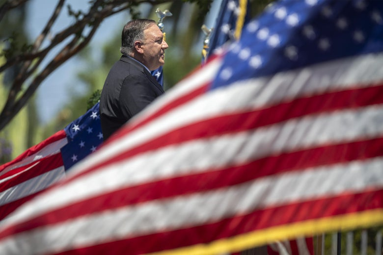 Mike Pompeo surrounded by American flags.