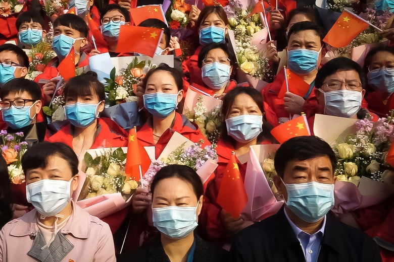 A crowd of Chinese people all wearing surgical masks and holding up little Chinese flags