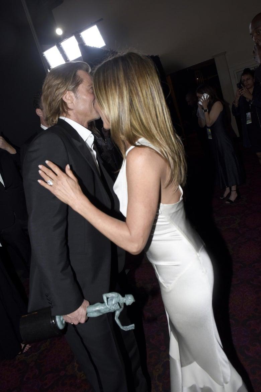 Jennifer Aniston leans in toward Brad Pitt to tell him something.