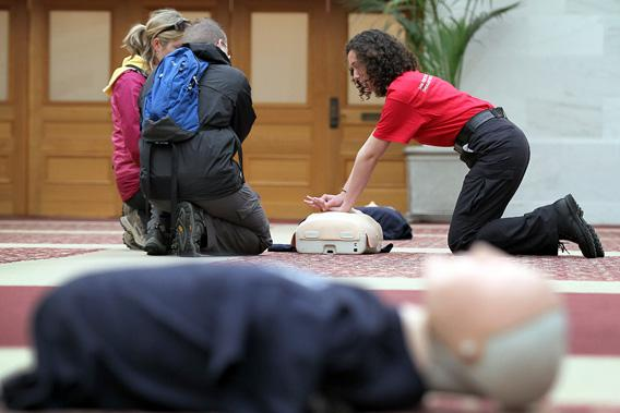 A volunteer with the San Francisco Paramedic Association teaches a couple how to perform CPR using a mannequin on June 1, 2011 in San Francisco, California.