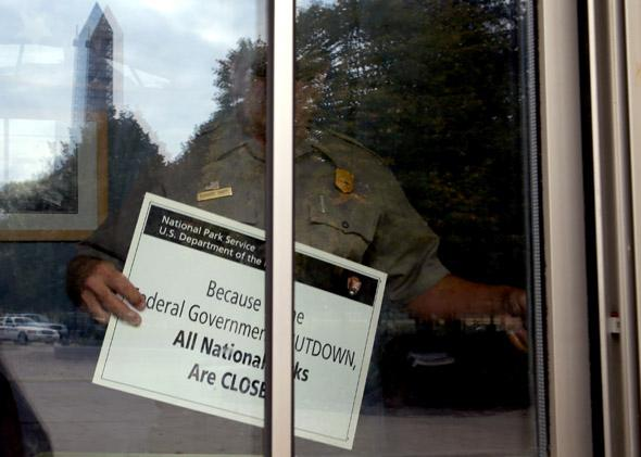 U.S. Park Service employee puts a closed sign in the window of the World War II Memorial ticket office on the National Mall October 1, 2013 in Washington, DC.
