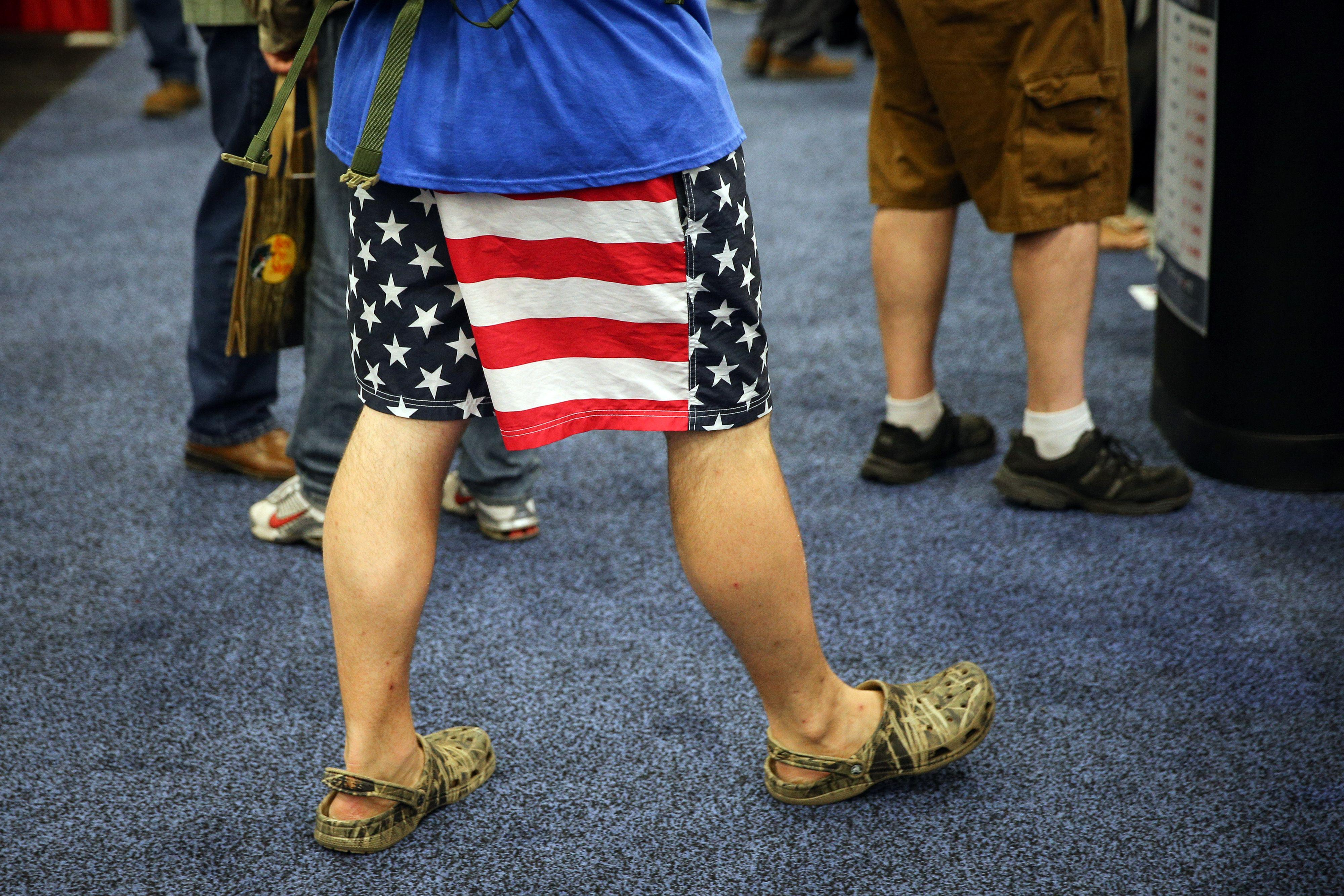 A man wears American flag shorts and camouflage Crocs.