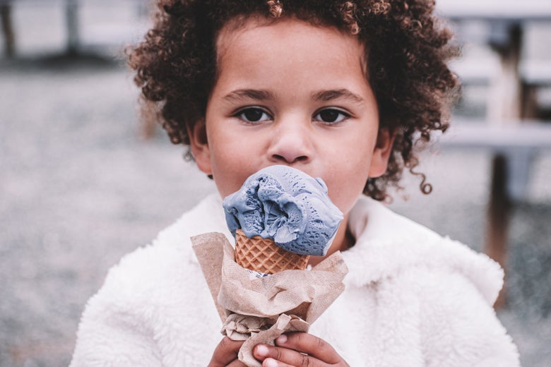 A young girl eating ice cream from a cone