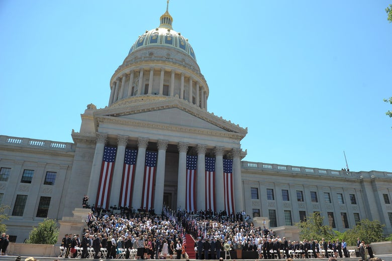 People gather for a ceremony in front of the West Virginia State Capitol in Charleston, West Virginia.