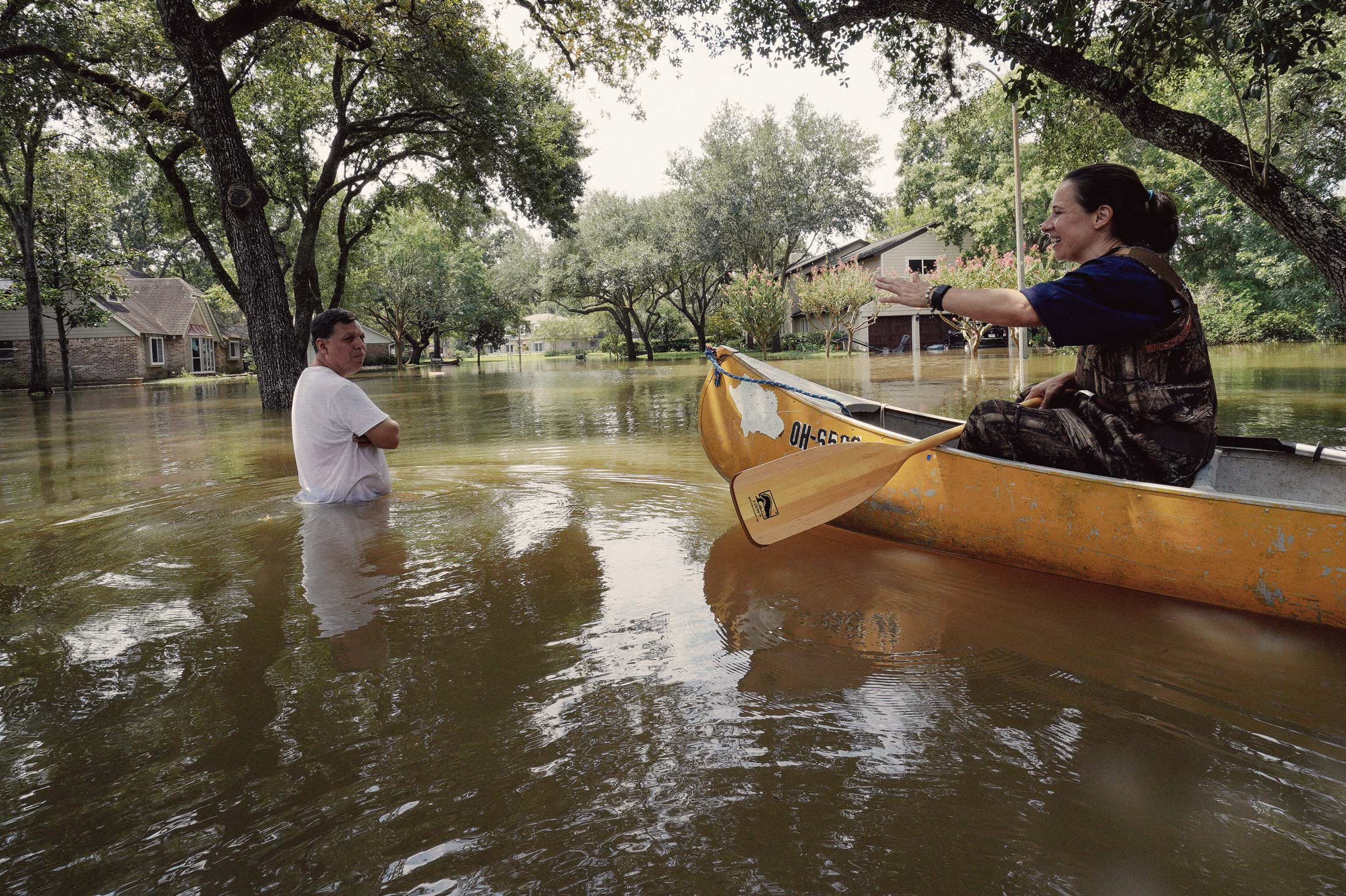 A woman in a canoe talks to a man standing in hurricane floodwaters. Houses and trees are partially submerged in the background.