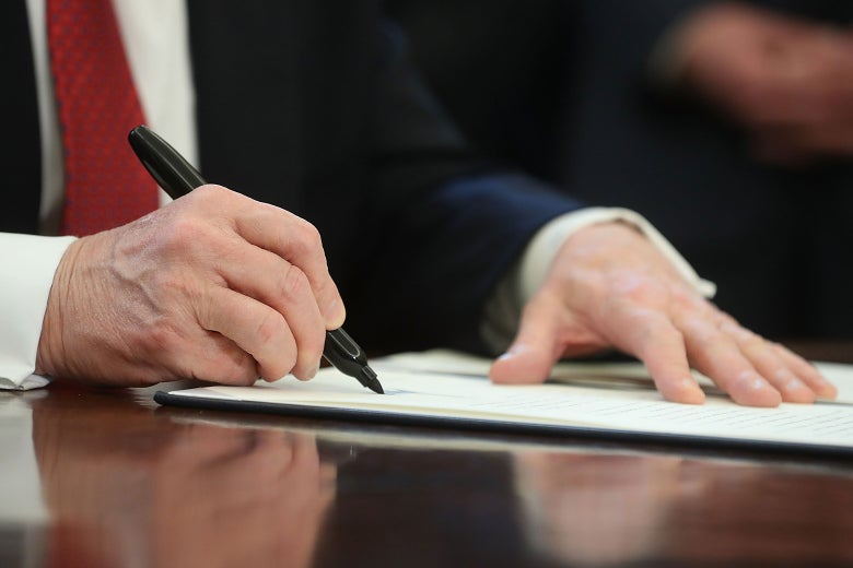 Trump signing a paper with a pen.
