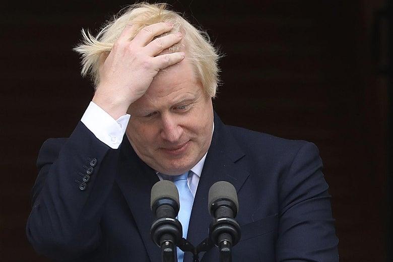 Boris Johnson exasperatedly runs his hands through his hair at a podium.