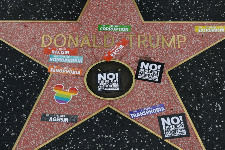 Donald Trump's Hollywood Walk of Fame star covered with stickers protesting ageism, corruption, racism, transphobia, and more. One sticker is shaped like Mickey Mouse and shows the colors of the gay pride flag.