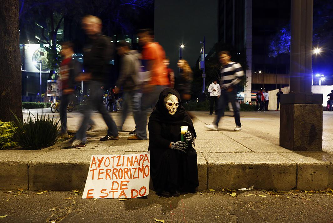 "A masked protester sits on a sidewalk holding a candle after the Nov. 8 protest. The sign reads ""Ayotzinapa, state terrorism""."