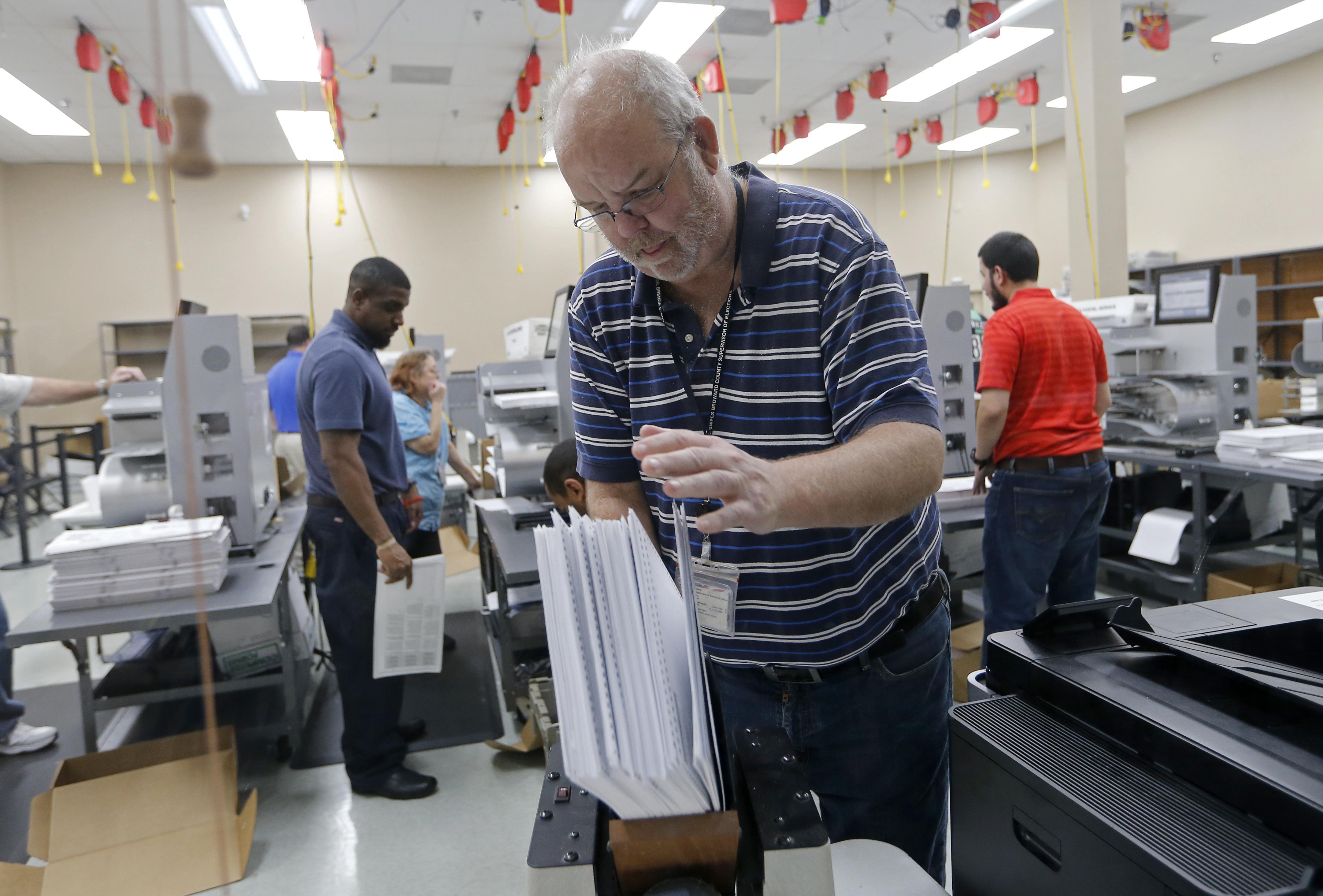 A Broward County election official arranges ballots for a recount.