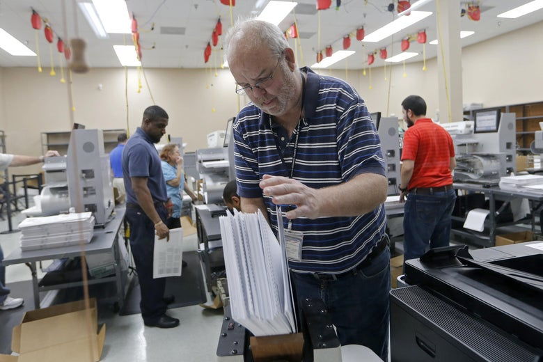 A Broward County election official arranges ballots for a recount.