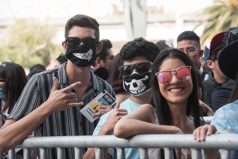 A crowd of concertgoers, some wearing face masks with skull imagery, outside on a sunny day