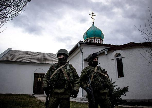Unmarked soldiers, widely understood to be Russian, wait outside a church on a Ukrainian military base in Perevalnoye.