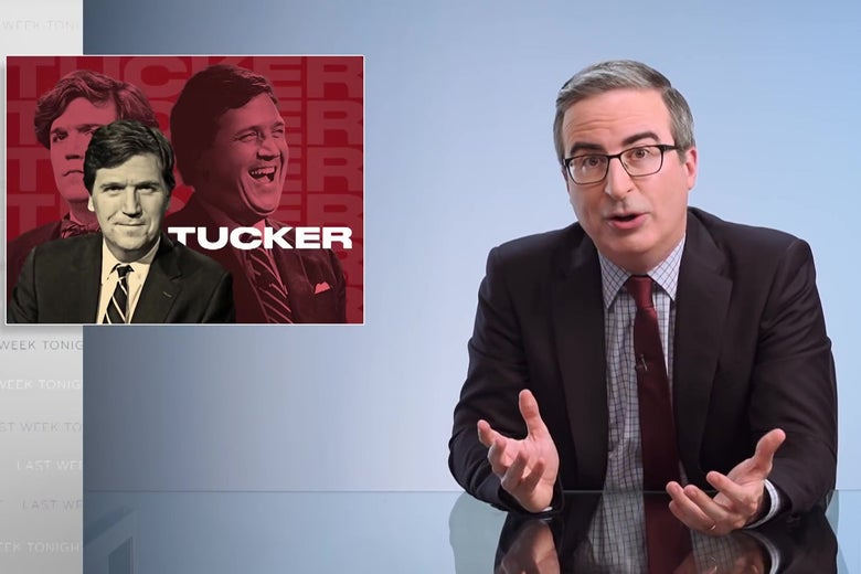 """John Oliver sits at his glass anchorperson's desk in front of a  sign reading """"Tucker,"""" with several photographs of Tucker Carlson."""