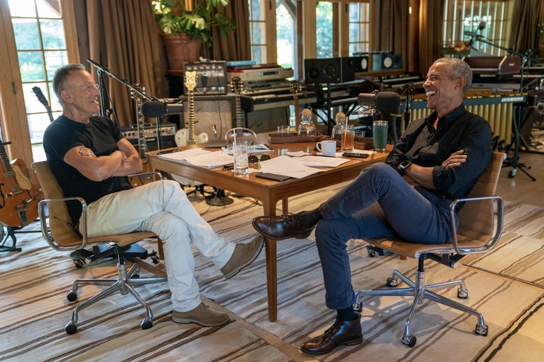 Bruce Springsteen and Barack Obama sit facing each other at a table covered in many beverages and papers. They are smiling into recording microphones. There are many musical instruments behind them.