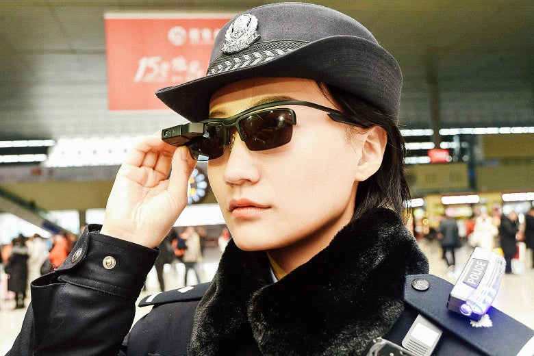 A female police officer wears a pair of smart glasses with a facial recognition system at a train station.