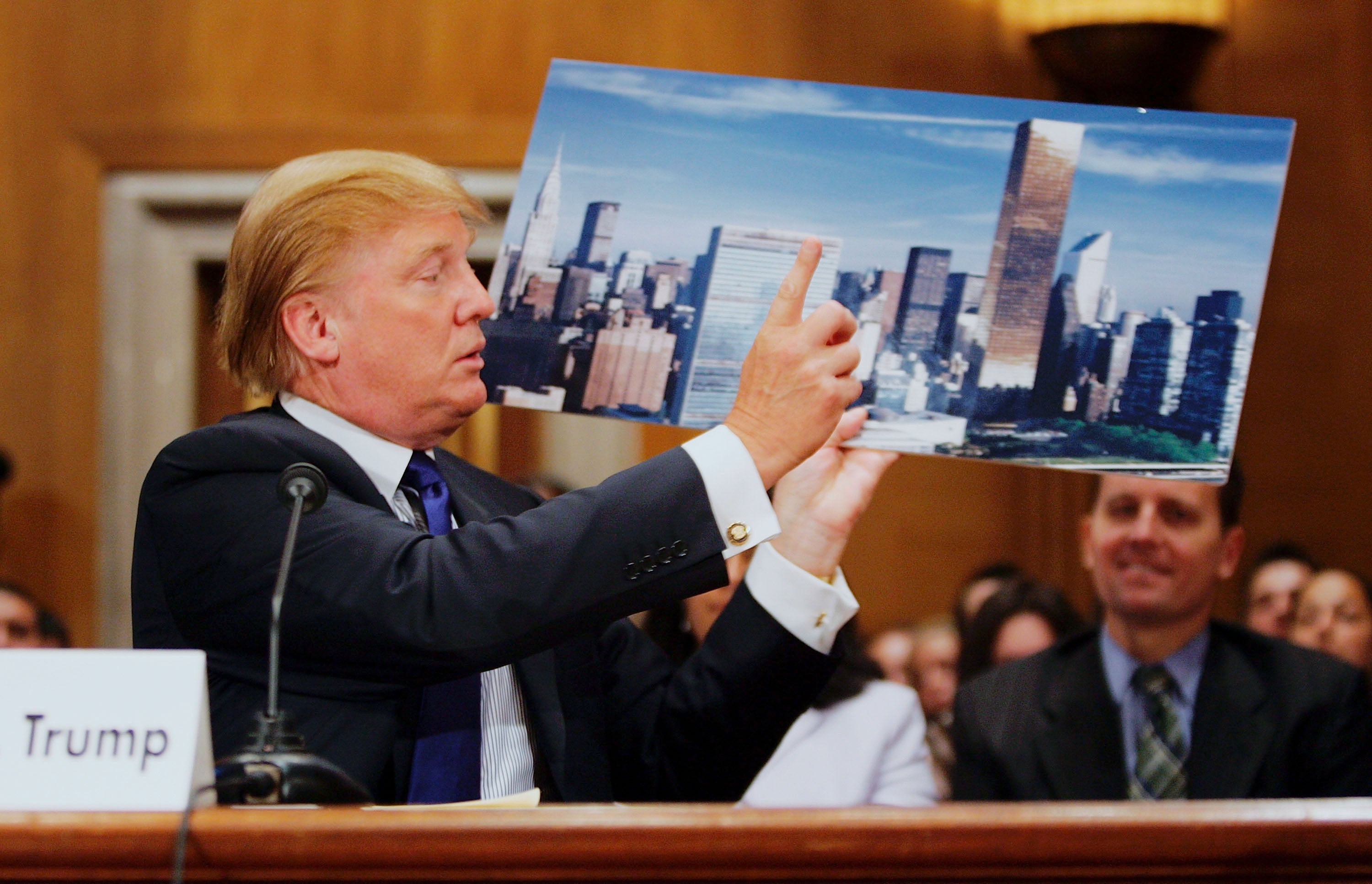 Donald Trump with a photo of the Trump World Tower, where the individual attesting to his alleged affair once worked, in Washington D.C. in 2005.