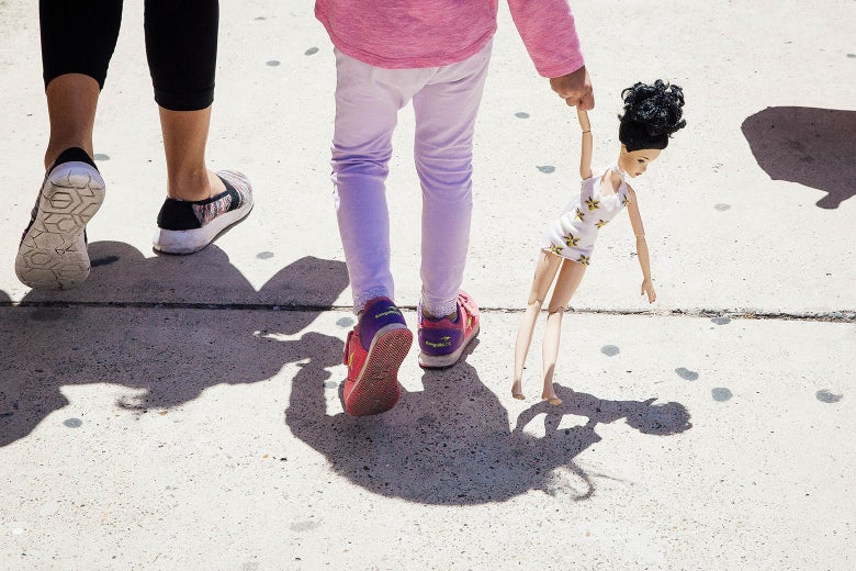 A 4-year-old Honduran girl carries a doll while walking with her immigrant mother.