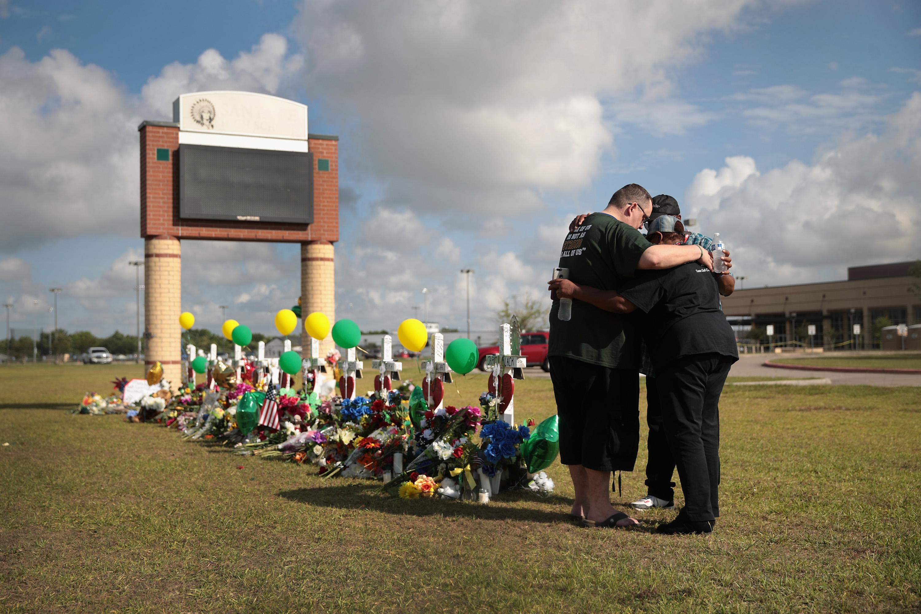 Mourners pray at a memorial in front of Santa Fe High School on May 22, 2018 in Santa Fe, Texas.