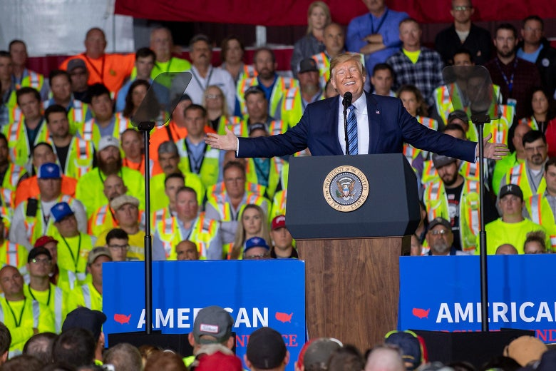 Trump speaking at a podium onstage with an audience of workers behind him.