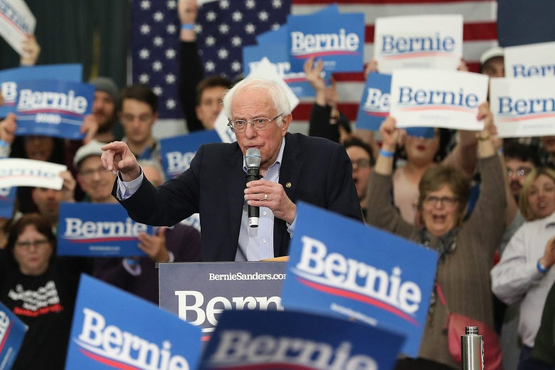 "Bernie Sanders at a rally with supporters behind him holding signs that say, ""Bernie."""