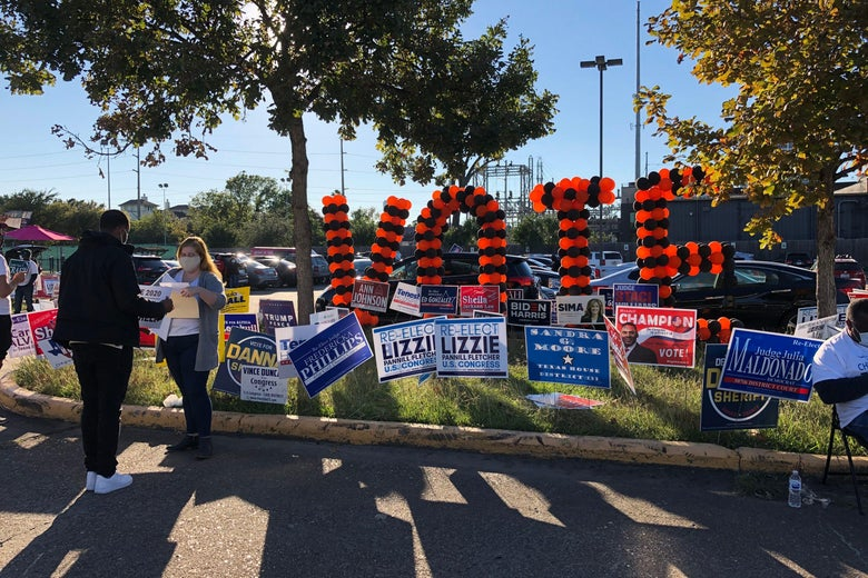 Big letters spelling out VOTE and a bunch of campaign signs on an island in a parking lot
