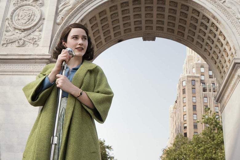 Rachel Brosnahan stands on front of a microphone wearing a green coat.