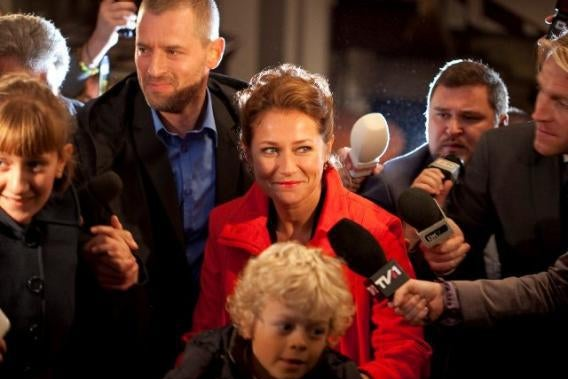 She smirks at the flashing cameras as a reporter holds out a microphone.