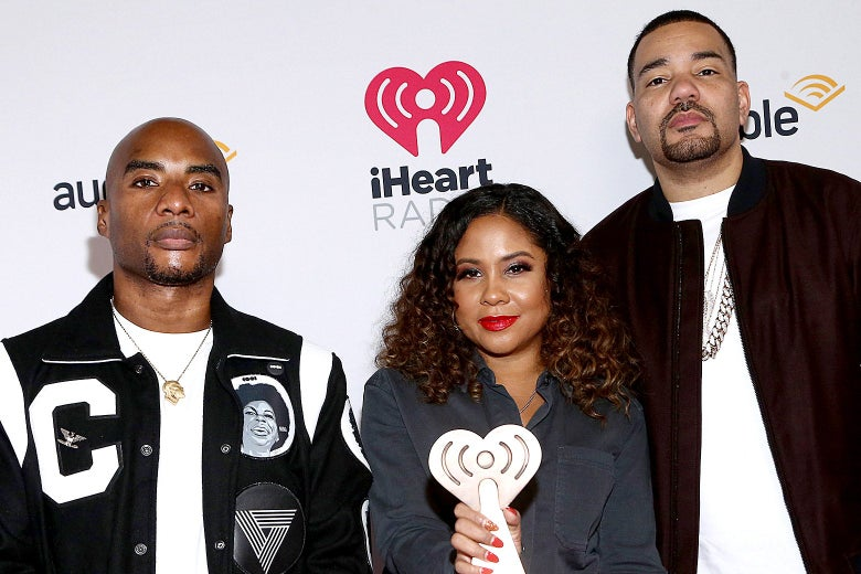 Angela Yee holds up a trophy with Charlamagne and Envy standing on either side of her in front of an Audible iHeartRadio step and repeat