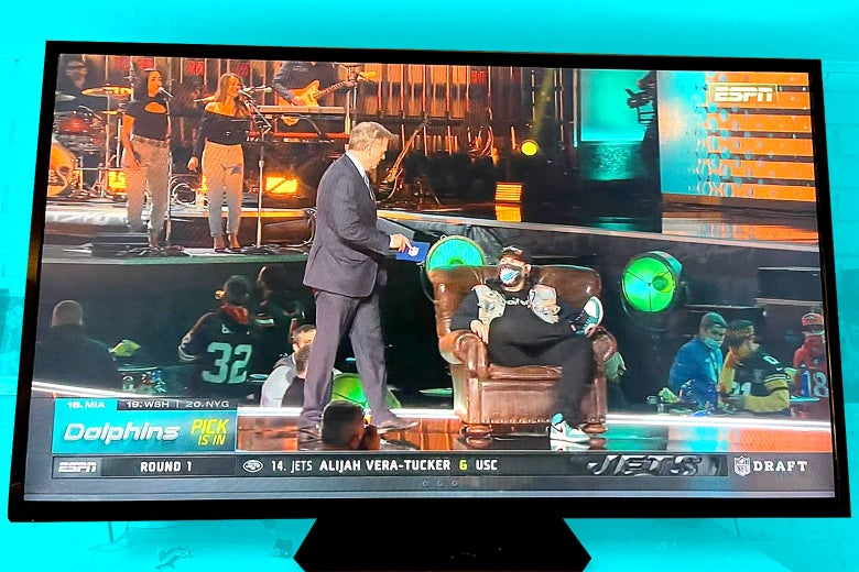 Goodell stands next to Smith, sitting in his chair, at the NFL Draft on flat-screen television