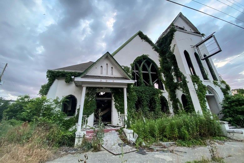 An abandoned church with ivy growing up the sides.