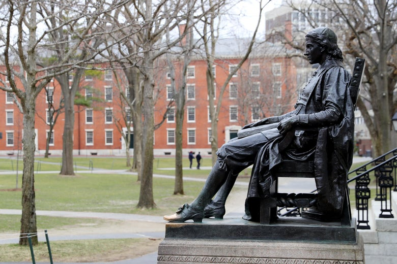 A statue overlooking a green space at Harvard.