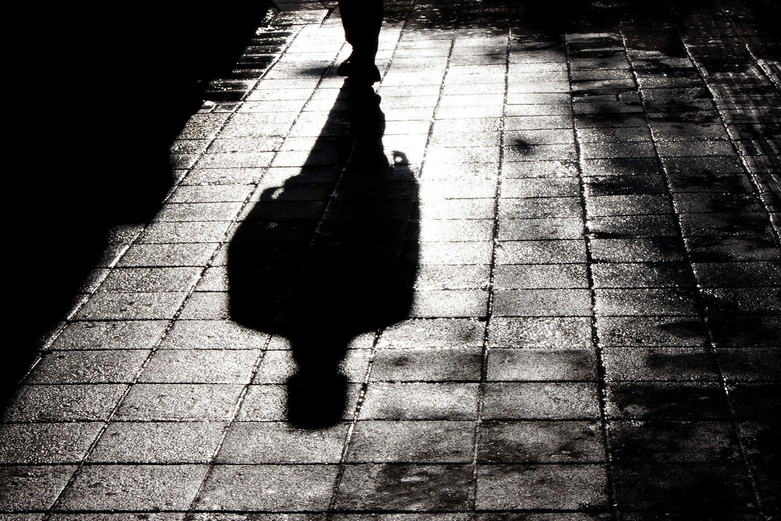 Shadow of a man walking down a dark street.
