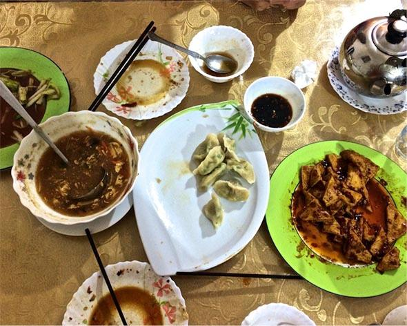 Hot and sour soup, chive and egg and meat dumplings, bok choy, home-style tofu, green tea, and emptied plates at Ruyi Fang off a side street in Maadi.