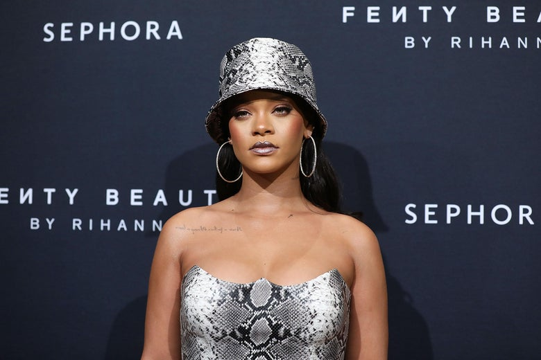 Rihanna stares straight ahead, wearing a bucket hat and large hoop earrings. Behind her are signs for Fenty Beauty and Sephora.