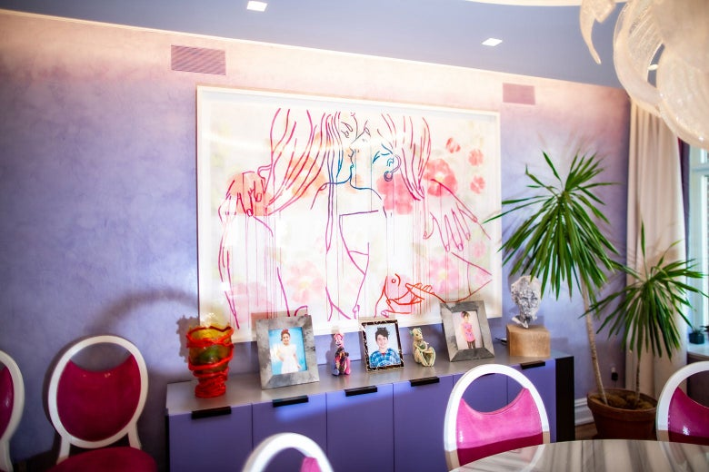 A piece of artwork in Rubenstein's home hangs over a purple credenza.