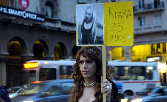 A transsexual person displays a poster with the picture of a transsexual person who was murdered.