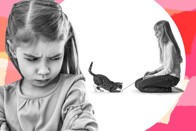 A young girl is seen pouting in front of another girl who is playing with a cat.