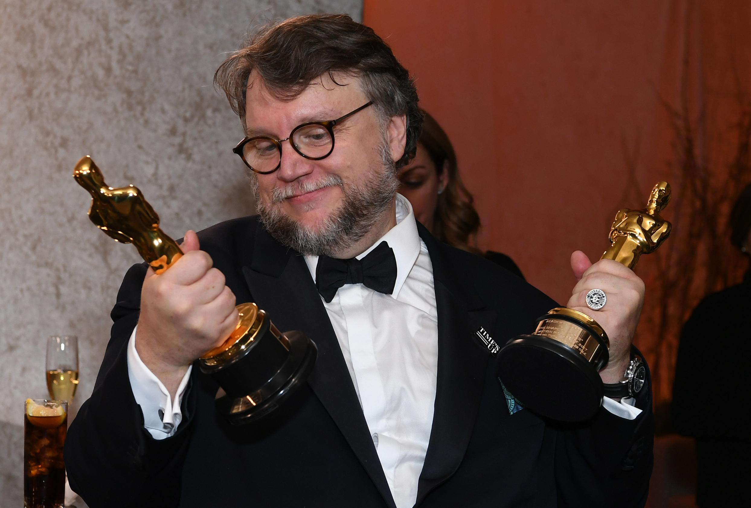 Guillermo del Toro, with an Oscar statuette in each fist.