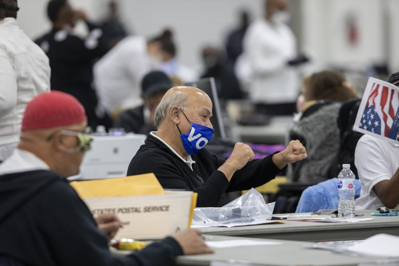 """A man wearing a """"VOTE"""" mask pumps his fists in a crowded room of people holding documents and ballots."""