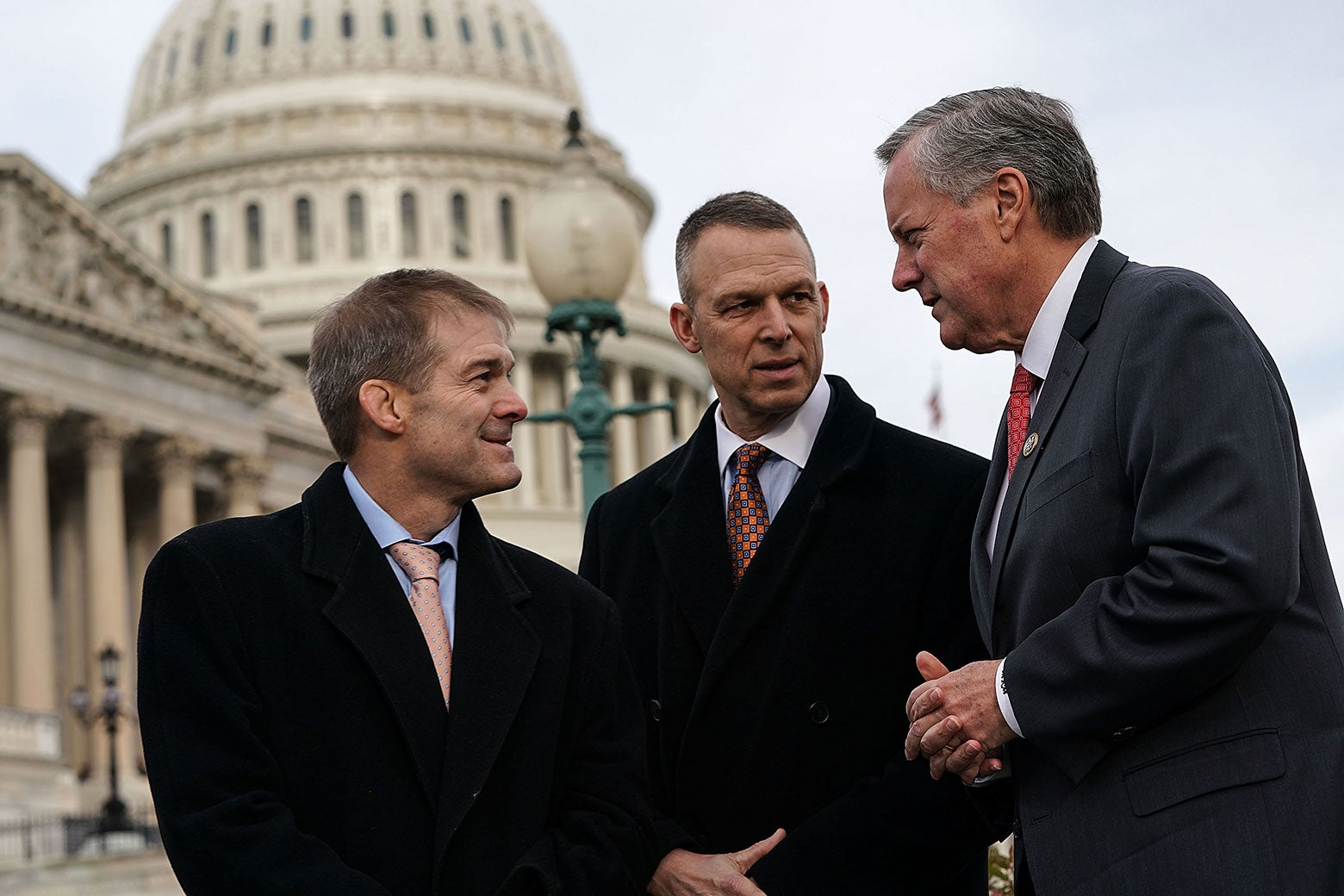 Three congressmen talk outside the Capitol Building.