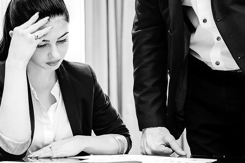 A woman in business attire stares down at some papers on a desk as a man stands over her.