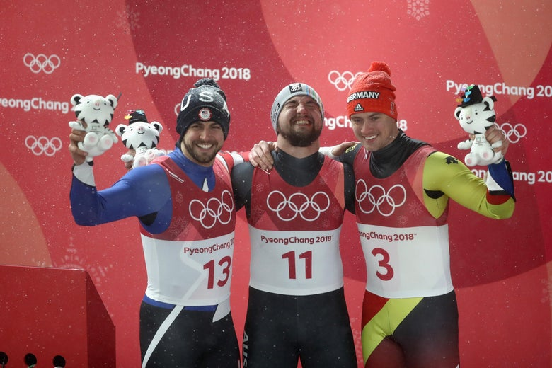 Chris Mazdzer (silver) of the United States, David Gleirscher (gold) of Austria, and Johannes Ludwig (bronze) of Germany celebrate at the flower ceremony.