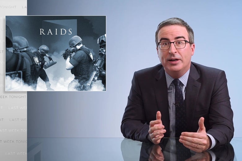 "John Oliver sits at his anchorperson desk, in front of a graphic reading ""Raids."""
