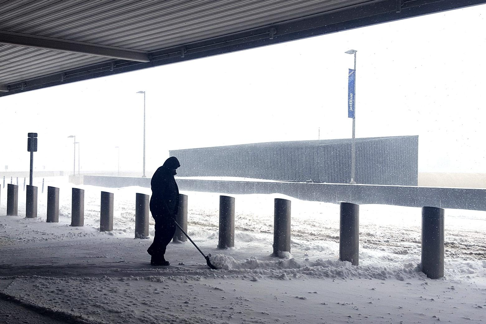 An airport employee shovels snow at the curb of the departures drop-off area.