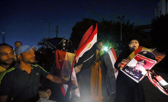 Egyptian women sell posters of Egypt's strongman, Defense minister Abdel Fattah el-Sissi and their country's flags in Cairo's landmark Tahrir Square.