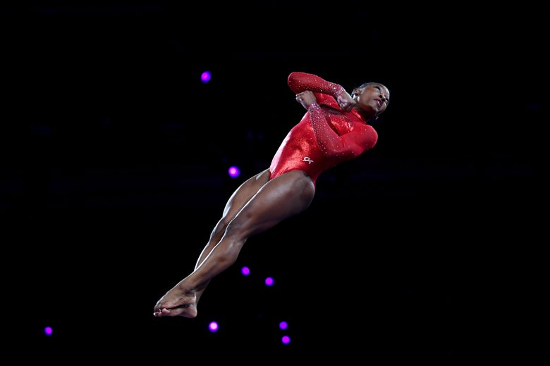 Simone Biles twisting in the air against a black background as she vaults.