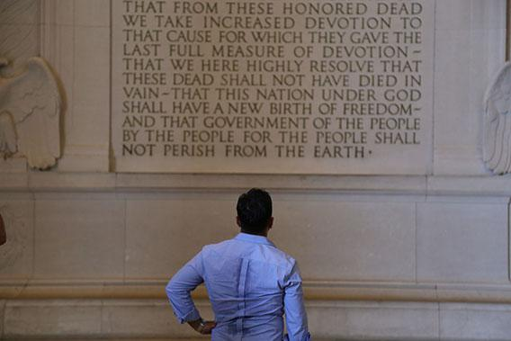 A tourist pauses in the Lincoln Memorial to read the Gettysburg Address.